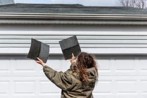 Young woman female homeowner standing in front of house garage in coat jacket during winter storm holding two roof tile shingles inspecting damage