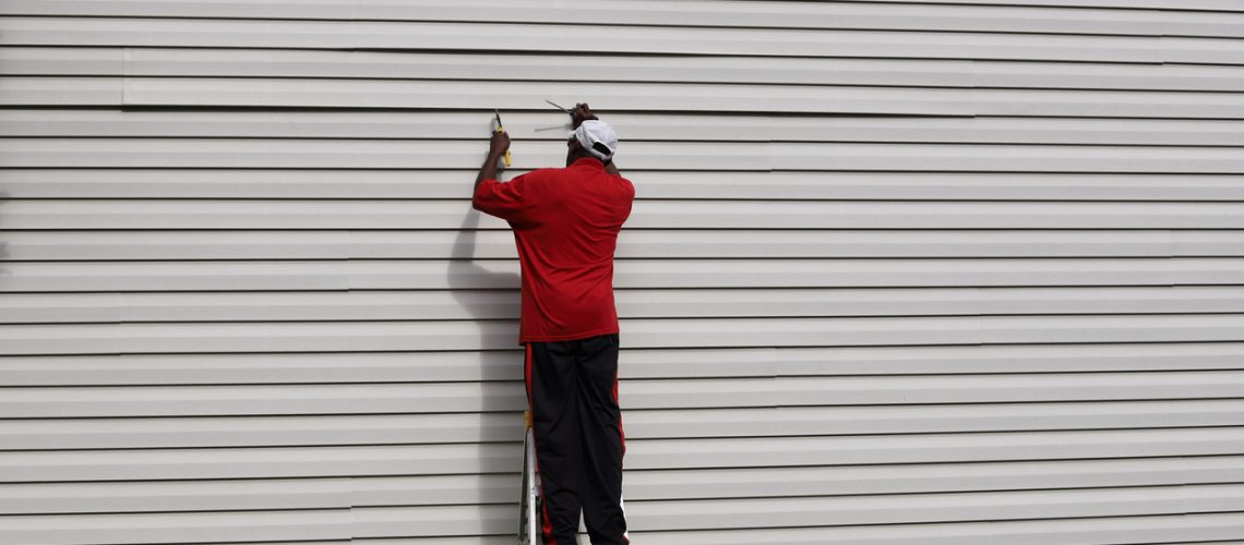An African-American man on a ladder and fixing vinyl siding on a house
