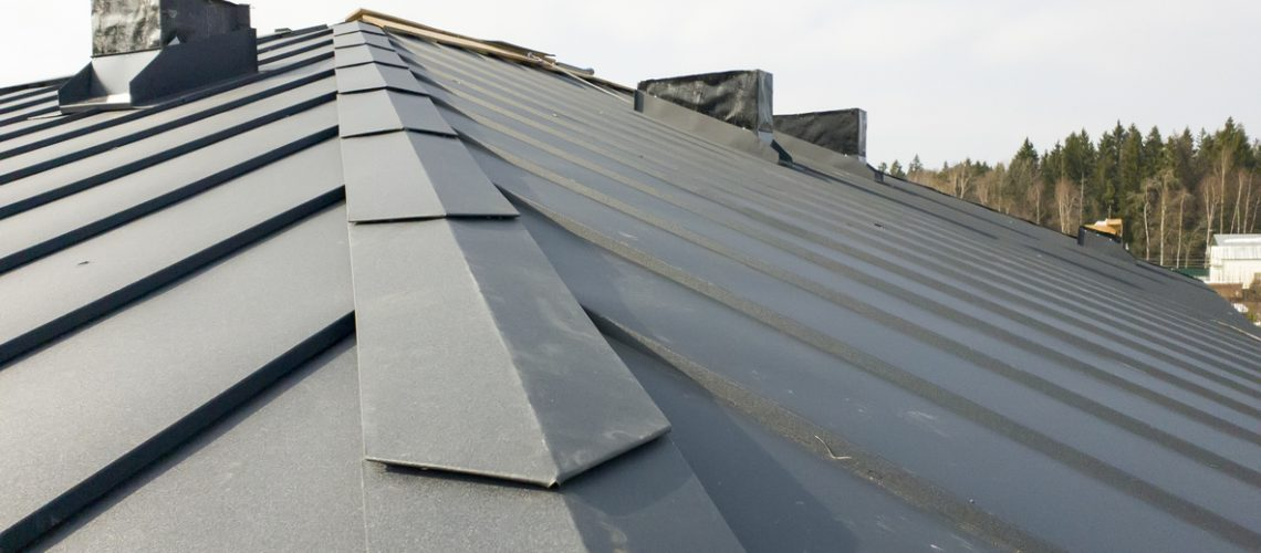 close up view of grey folding roof and chimney on waterproofing layer of house under construction