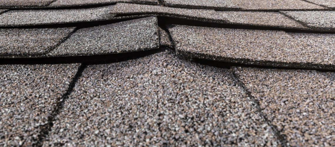 A close-up of a buckled residential asphalt shingled roof